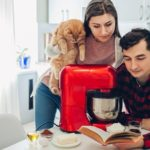 Young happy couple cooking on kitchen with food processor and holding cat. Woman and man reading recipe and hugging. Lifestyle