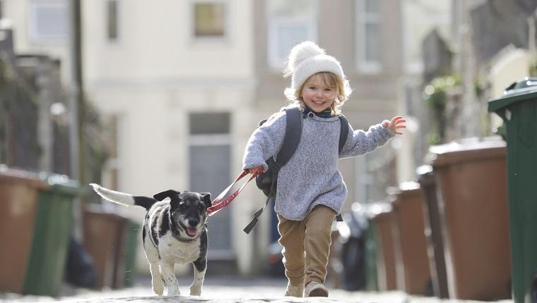 Kleinkind, das mit Hund läuft