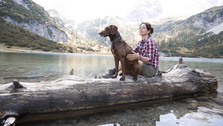 Österreich, Tirol, Frau mit Hund, der auf Baumstamm am Seebensee sitzt