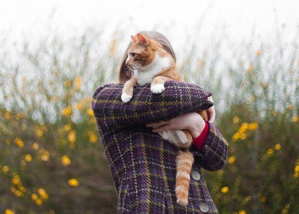 A blonde woman hugs her ginger cat outside. Her face is hidden by the cat.