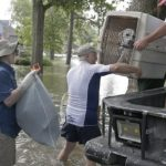 A father and son carry their dog as they evacuate from their homes the flood in Lakeside Estate in Houston, Texas on August 30, 2017. Monster storm Harvey made landfall again Wednesday in Louisiana, evoking painful memories of Hurricane Katrina