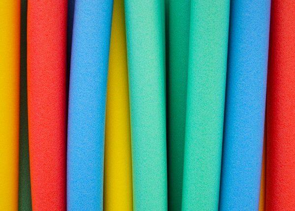 Studio photograph of colorful foam floating swim noodles.