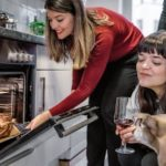 beautiful young woman with dog checking christmas poultry in the oven