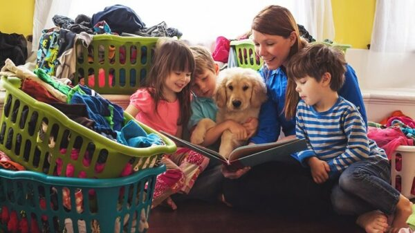 Smiling mother reading to three children and golden retriever puppy dog surrounded by laundry baskets