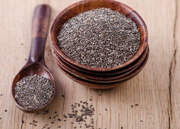 Stack of wooden bowl with chia seeds and wooden spoon on wood