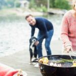 Happy woman using mobile phone while barbecuing with man and dog in background on pier