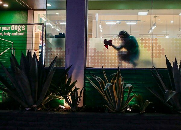 West Hollywood, CA, Wednesday, November 25, 2020 - A worker cleans windows at the Healthy Spot pet spa hours before Covid restrictions require restaurants close at 10 pm, leaving the usually bustling Santa Monica Blvd., less populated.