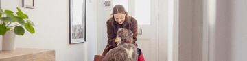 Frau, die mit Trennungsangst in der Tür streichelt Hund